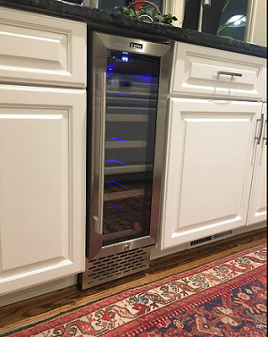photo showing the Colzer 18 bottle wine fridge built under the counter between white kitchen cabinets.