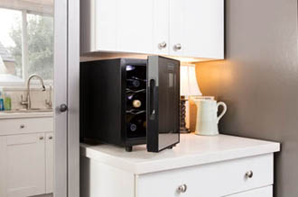 a black 6 bottle wine cooler placed on a white kitchen counter, the glass door is partially open, we can see som of the bottles lying on the contoured metal shelves