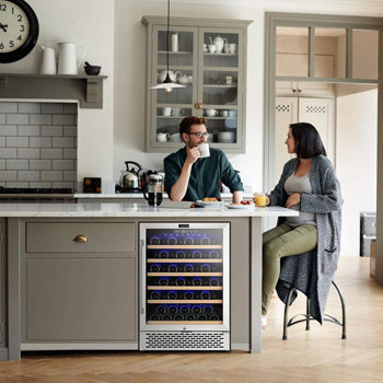 photo of a modern kitchen with a young couple having coffe at the island. the Colzer 51 bottle fridge is can be seen built-in under the counter