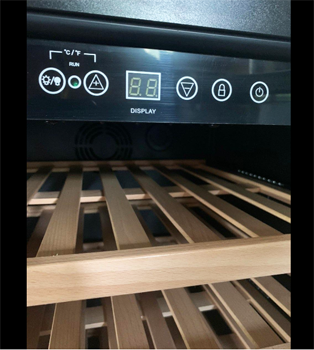 photo of the Colzer 51 bottle cooler's control panel and an empty wooden shelf