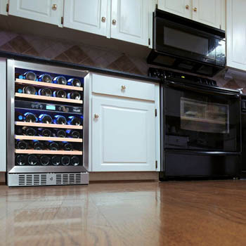 photo showing the NewAir 46-bottle wine refrigerator built-in under the kitchen counter within white wood cabinetry